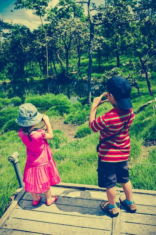 Vue arrière des enfants asiatiques détendant dehors pendant la journée, TR image stock