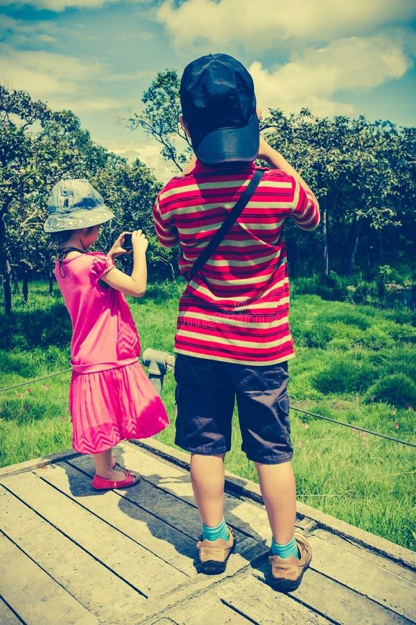 Vue arrière des enfants asiatiques détendant dehors pendant la journée, TR photo libre de droits