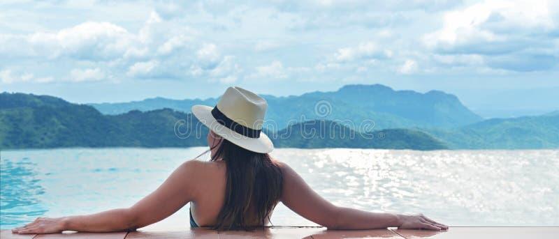 Vue arrière des femmes heureuses de mode de vie détendre et apprécier dans la piscine regardant le paysage de montagne d'extérieu photos libres de droits