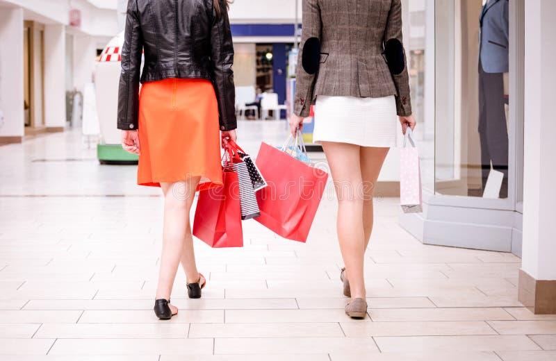 Vue arrière des femmes marchant dans le mail avec des paniers photo stock