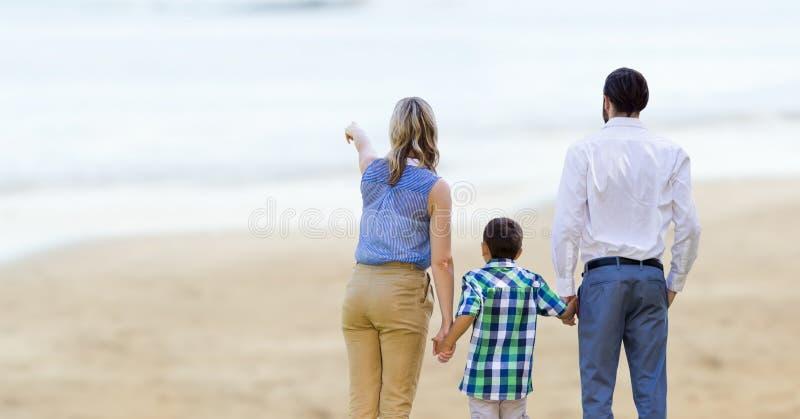 Vue arrière des parents avec des enfants sur la plage photo stock