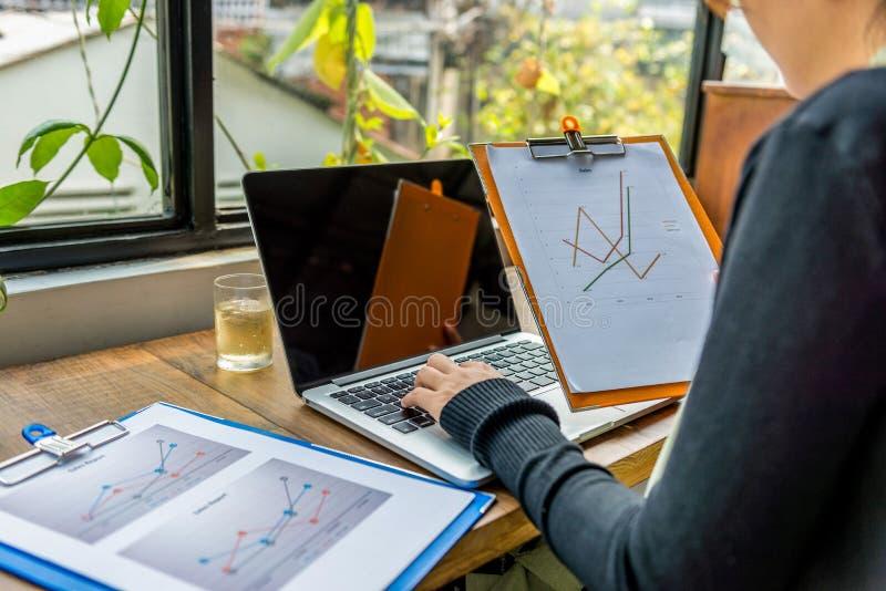 Vue arrière du diagramme de participation de femme, ordinateur portable de dactylographie près de fenêtre photographie stock