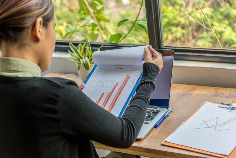 Vue arrière du document de graphique de participation de femme à côté de la fenêtre photographie stock