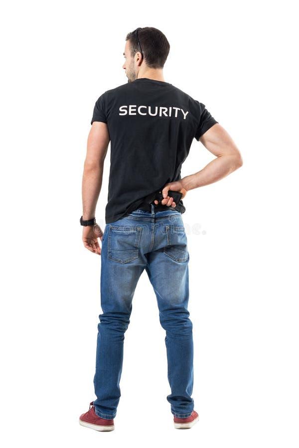 Vue arrière du flic secret ou de l'agent de sécurité alerté atteignant l'arme à feu de main attachée sur la ceinture images stock