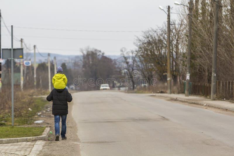 Vue arrière du père sportif fort d'homme continuant l'enfant en bas âge d'épaules dans l'habillement lumineux chaud marchant le l photographie stock libre de droits