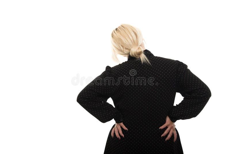 Vue arrière du professeur féminin blond montrant le geste de douleurs de dos photo stock