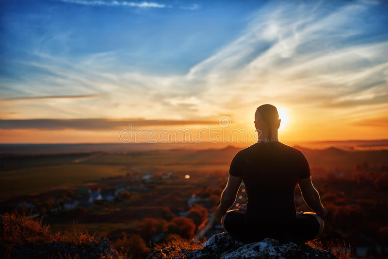 Vue arrière du yoga méditant d'homme dans la pose de lotus sur la roche au coucher du soleil photographie stock libre de droits