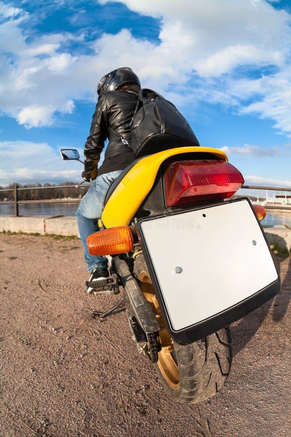Vue arrière et grande-angulaire à la plaque minéralogique vide claire du vélo, cavalier s'asseyant sur la motocyclette photos libres de droits