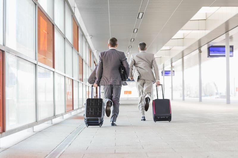 Vue arrière intégrale des hommes d'affaires avec le bagage fonctionnant sur la plate-forme de chemin de fer images stock