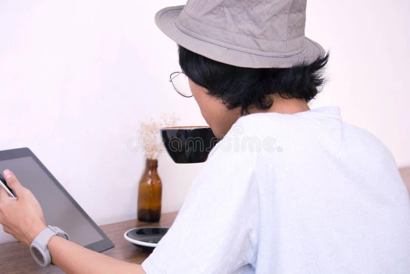 Vue arrière Jeune homme créatif dans la chemise blanche et le chapeau de padora se reposant à la table, utilisant l'ordinateur po images libres de droits