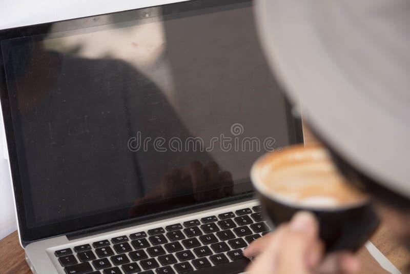 Vue arrière Jeune homme créatif dans la chemise blanche et le chapeau de padora se reposant à la table, utilisant l'ordinateur po image libre de droits