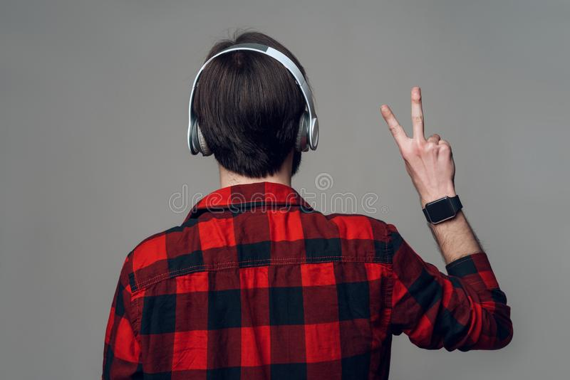 Vue arrière musique de écoute d'homme d'écouteurs à photographie stock libre de droits