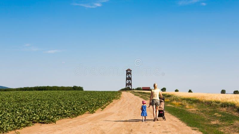 Vue arrière sur la femme marchant avec la petite fille image libre de droits