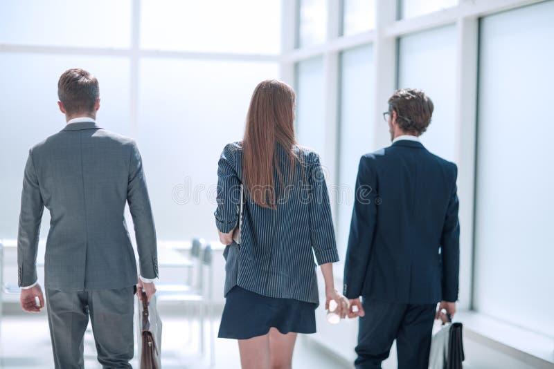 Vue arrière un groupe d' hommes d' affaires marchant dans le couloir de bureau image stock