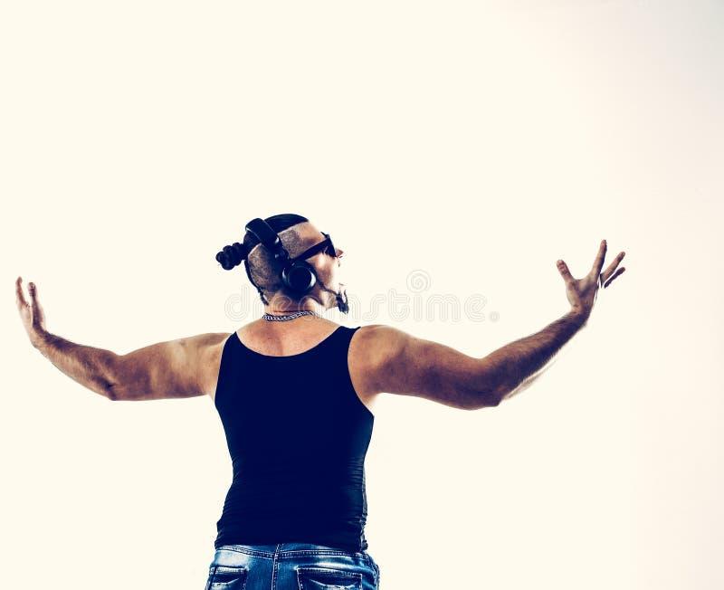 Vue arri?re - bodybuilder ?motif avec des ?couteurs et des lunettes de soleil image libre de droits