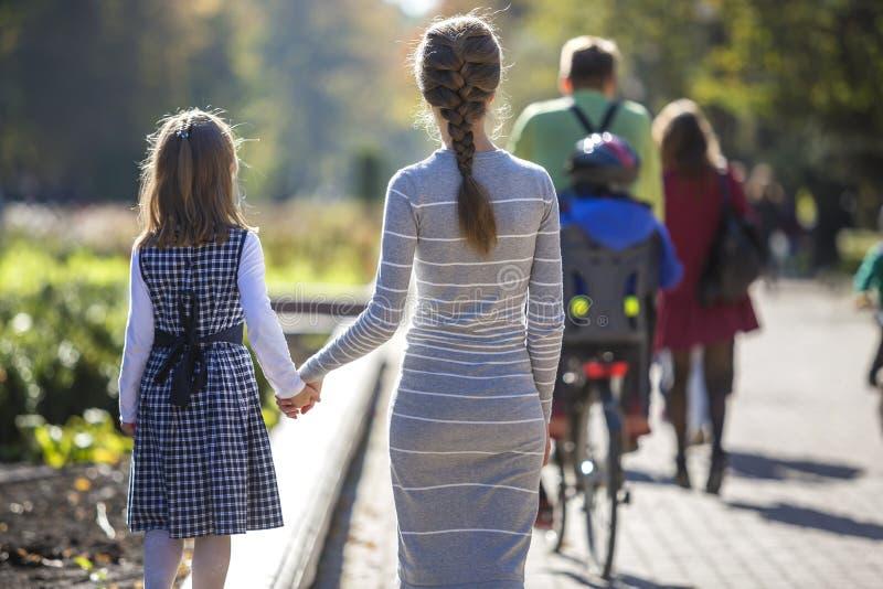 Vue arri?re de fille et de m?re d'enfant dans des robes tenant ensemble des mains sur l'ext?rieur chaud de jour sur le fond ensol photographie stock libre de droits