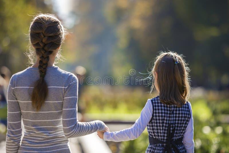 Vue arri?re de fille et de m?re d'enfant dans des robes tenant ensemble des mains sur l'ext?rieur chaud de jour sur le fond ensol photo stock