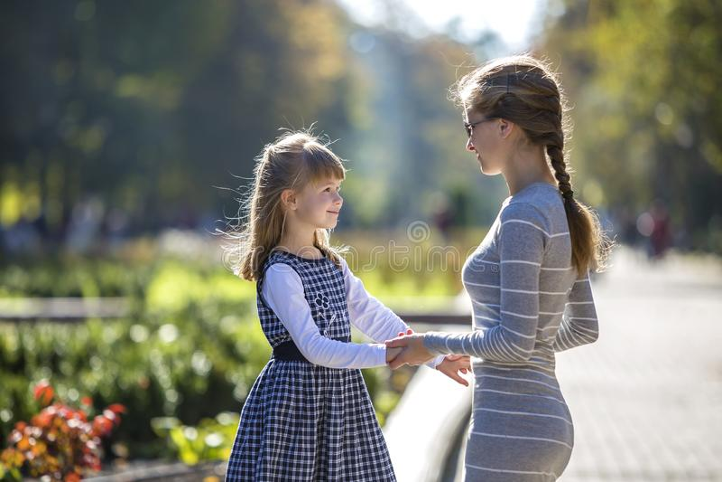 Vue arri?re de fille et de m?re d'enfant dans des robes tenant ensemble des mains sur l'ext?rieur chaud de jour sur le fond ensol photos stock