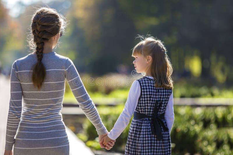 Vue arri?re de fille et de m?re d'enfant dans des robes tenant ensemble des mains sur l'ext?rieur chaud de jour sur le fond ensol image stock
