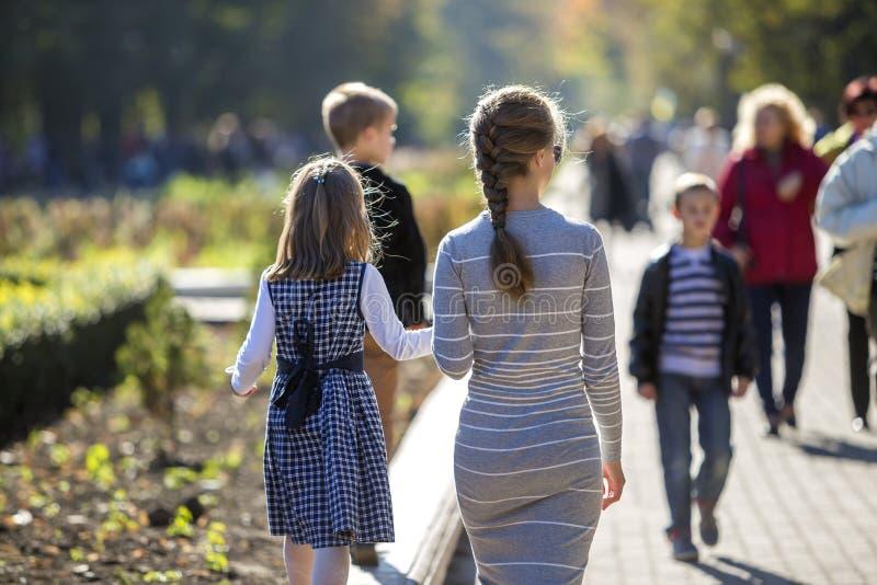 Vue arri?re de fille et de m?re d'enfant dans des robes tenant ensemble des mains sur l'ext?rieur chaud de jour sur le fond ensol photos libres de droits
