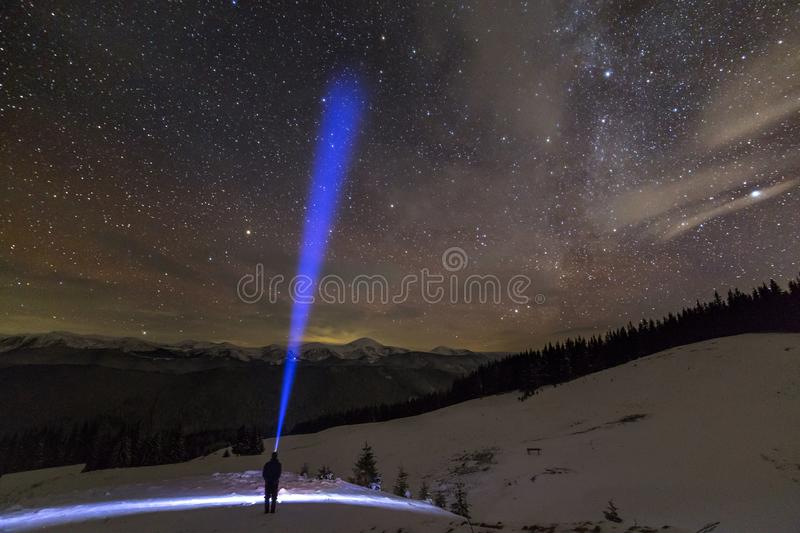 Vue arri?re de l'homme avec la position principale de lampe-torche sur la vall?e neigeuse sous le ciel ?toil? de bel hiver bleu-f image stock