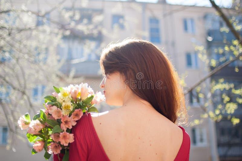 Vue arri?re de la jeune femme ?tonnante et belle tenant un grand bouquet des fleurs color?es dehors pr?s des b?timents dessus image libre de droits