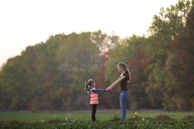 Vue arri?re de la jeune position attrayante mince de fille de m?re et d'enfant dans le pr? vert jugeant des mains dehors sur des  images libres de droits