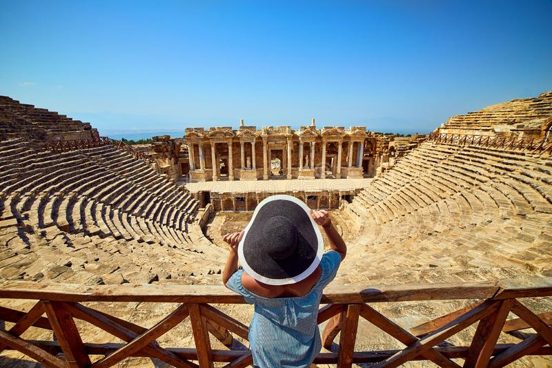 Vue arri?re de voyageuse de femme dans le chapeau regardant des ruines stup?fiantes d'amphith??tre dans Hierapolis antique, Pamuk images libres de droits
