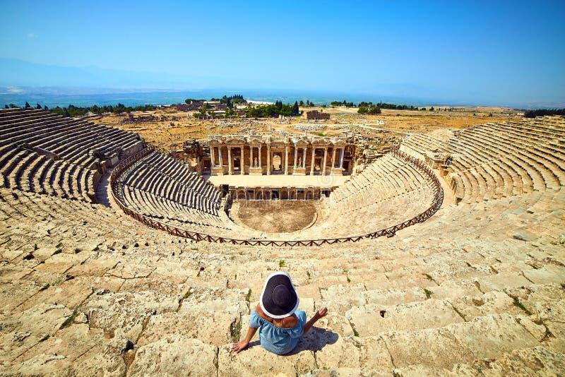 Vue arri?re de voyageuse de femme dans le chapeau regardant des ruines stup?fiantes d'amphith??tre dans Hierapolis antique, Pamuk photo libre de droits