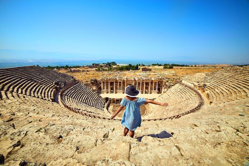 Vue arri?re de voyageuse de femme dans le chapeau regardant des ruines stup?fiantes d'amphith??tre dans Hierapolis antique, Pamuk photographie stock