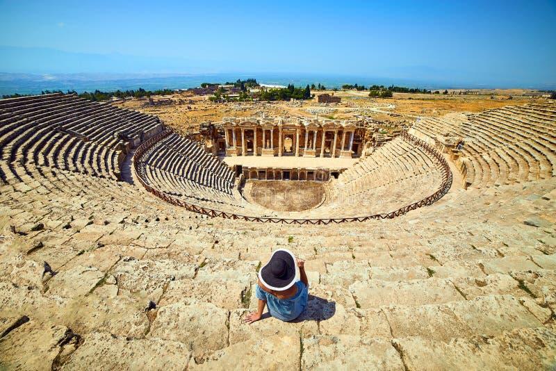 Vue arri?re de voyageuse de femme dans le chapeau regardant des ruines stup?fiantes d'amphith??tre dans Hierapolis antique, Pamuk photos stock