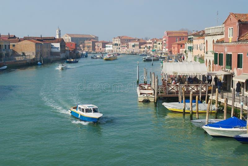 Vue au canal grand, aux bateaux, aux bâtiments et aux personnes à la rue en premier ressort dans Murano, Italie photo libre de droits