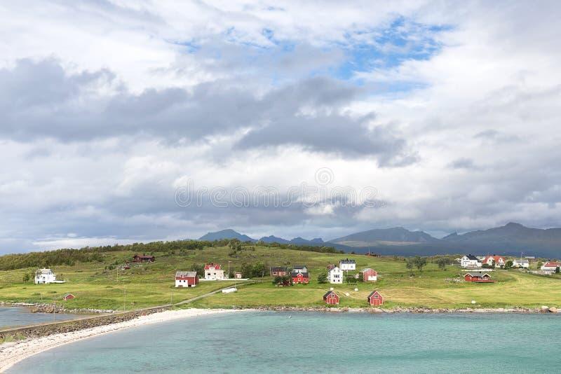 Vue au-dessus d'un fjord norvégien vers une île avec les huttes de pêche et le r images stock