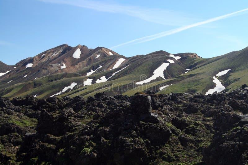 Vue au-dessus de champ avec la cendre volcanique noire de lave sur la gamme de montagne avec des taches de la neige et de la glac photo libre de droits
