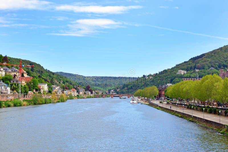 Vue au-dessus de la rivière Neckar avec de vieux bâtiments historiques et chaîne de montagne d'Odenwald au-dessus d'Heidelberg en image libre de droits