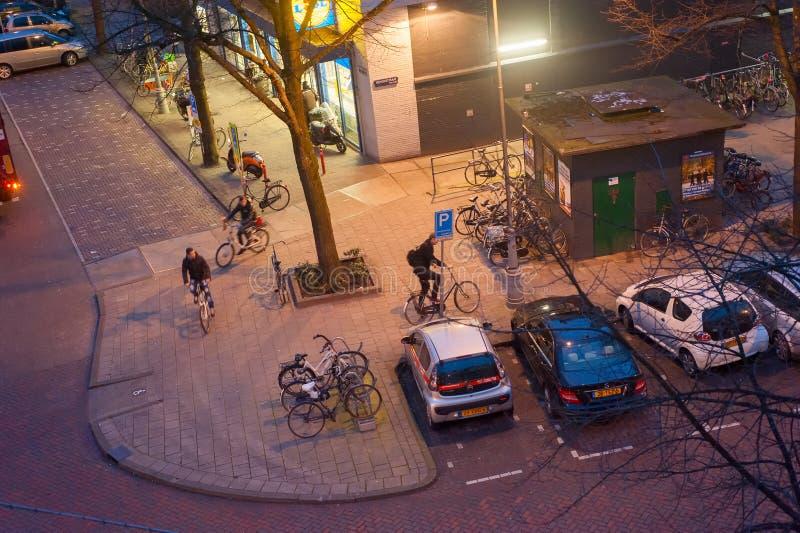Vue au-dessus de rue d'Amsterdam avec le stationnement de bicyclette et de voitures illuminé le soir, Pays-Bas image stock