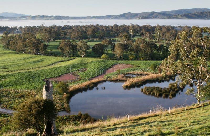 Vue au-dessus des terres cultivables avec des arbres et d'un barrage, collines brumeuses le long de l'horizon images libres de droits