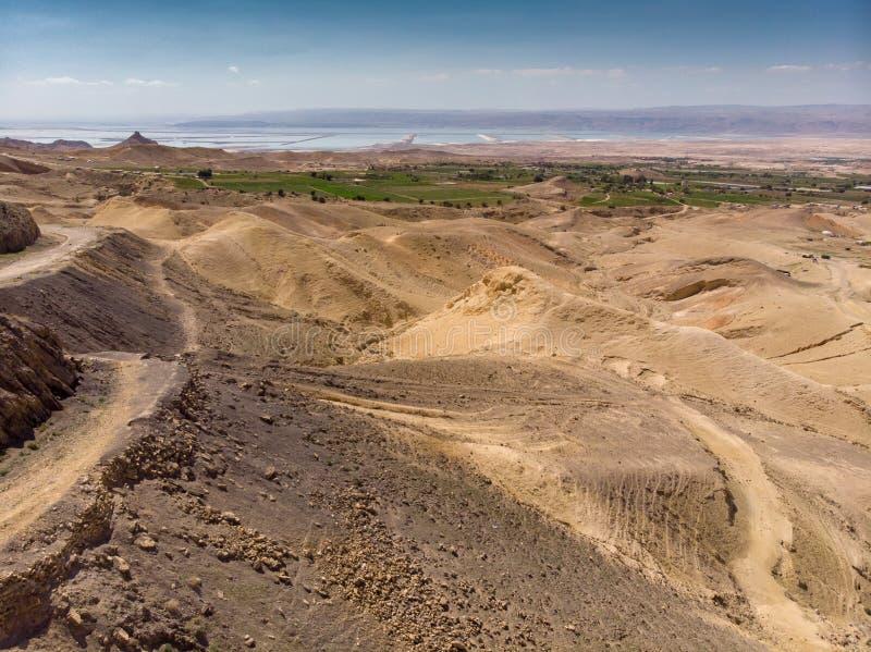 Vue au-dessus du désert jordanien au-dessus des plantations irriguées et des salines à la mer morte avec la côte de l'Israël dans image stock