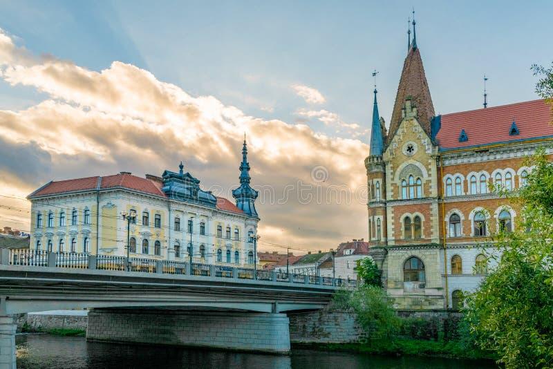 Vue au palais de Babos - quitté - et palais de Szeki - idéologiquement correct le rivage de Somesul Mic River à Cluj-Napoca, Roum photos stock
