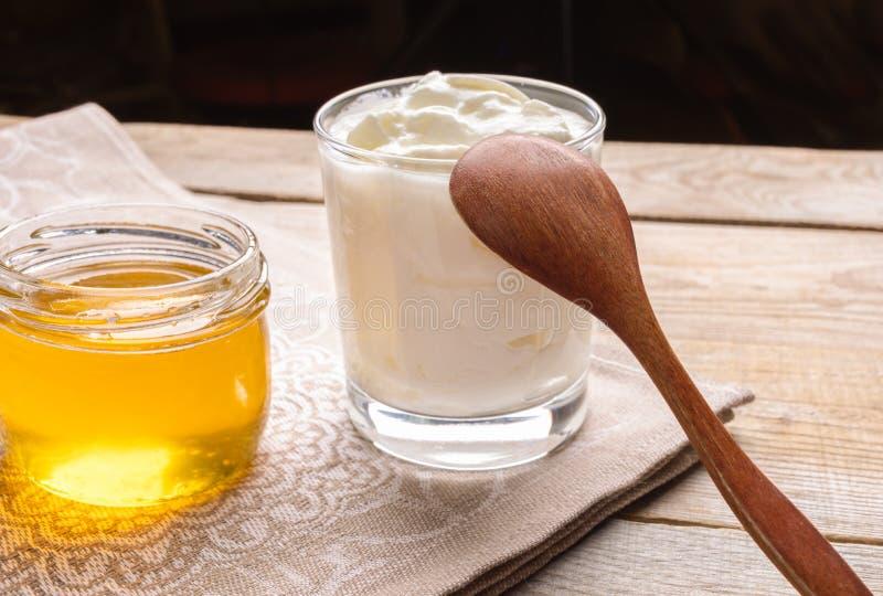Vue au verre du yaourt, et du pot avec du miel sur la serviette de cuisine sur la table en bois images libres de droits