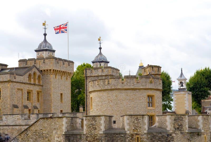 Vue aux parties de la tour de Londres avec Union Jack du côté de terre à un jour nuageux photographie stock libre de droits