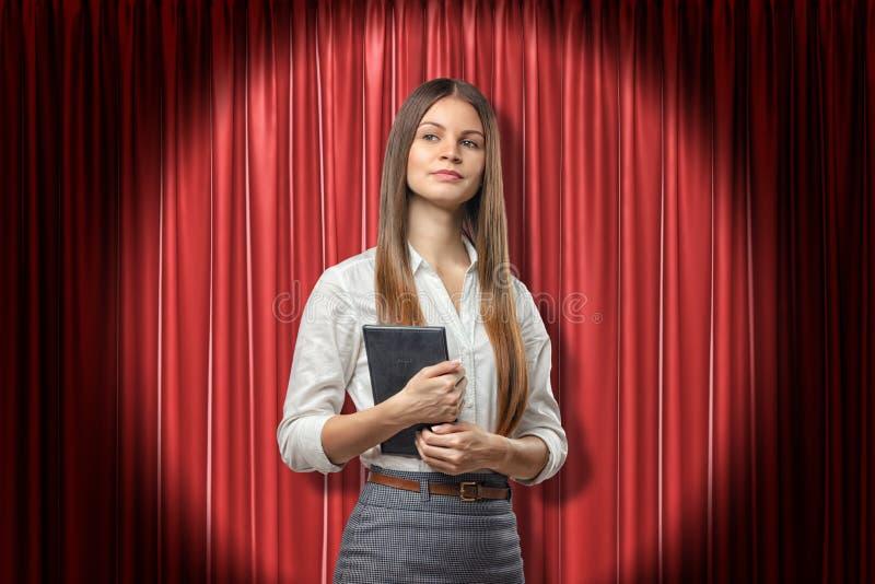 Vue avant de culture de la jeune femme d'affaires attirante tenant la position quotidienne de planificateur dans le projecteur co images stock