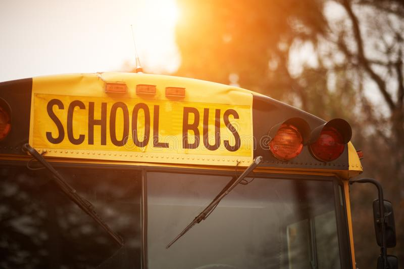 Vue avant de plan rapproché de signe jaune de pare-brise d'autobus scolaire au coucher du soleil photos stock