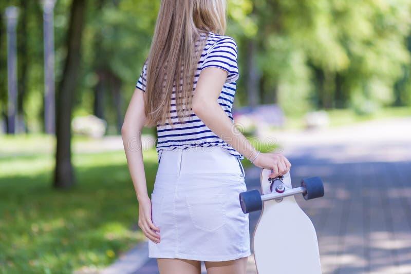 Vue blonde femelle de dos d'adolescent Pose avec Longboard dehors photo libre de droits