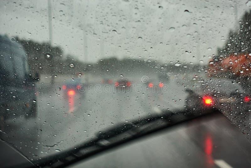 Vue brouillée de circulation routière un jour pluvieux par la fenêtre de voiture image stock