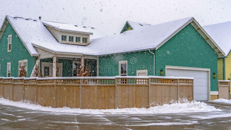 Vue claire d'hiver de panorama d'une maison color?e avec la barri?re en bois contre le ciel nuageux dans l'aube images libres de droits