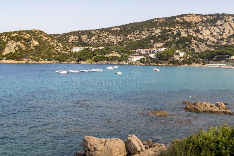 Vue colorée regardant la plage de Cala Batistoni et un océan méditerranéen de turquoise avec la côte et les pédalos de granit : B photos libres de droits