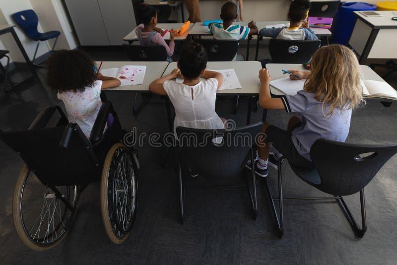 Vue courbe d'écolière de débronchement avec des camarades de classe étudiant et s'asseyant au bureau dans la salle de classe images libres de droits