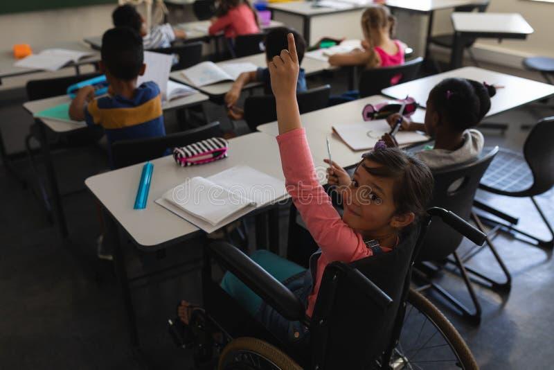 Vue courbe d'écolière de débronchement regardant la caméra et soulevant la main dans la salle de classe images stock