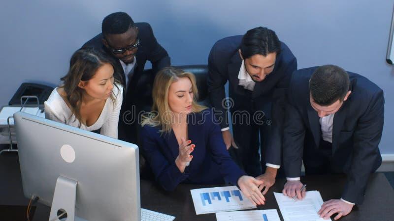 Vue courbe d'équipe créative se tenant autour de la table discutant des idées d'affaires images libres de droits